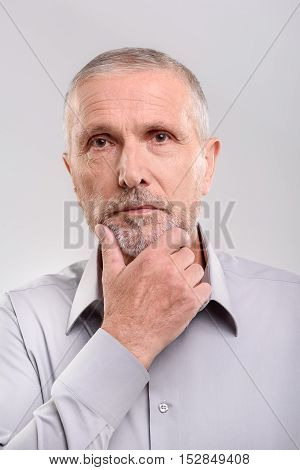 portrait of an old thoughtful man on gray background