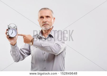 time is money son, mature business person points to the clock with copy space