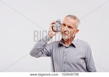 elderly man listening to an old vintage clock against a gray background
