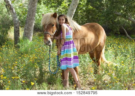 A cute little girl hugging her Icelandic Pony Friend.