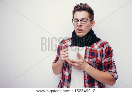 Man with flu and fever wrapped in scarf holding cup of healing tea isolated over white.