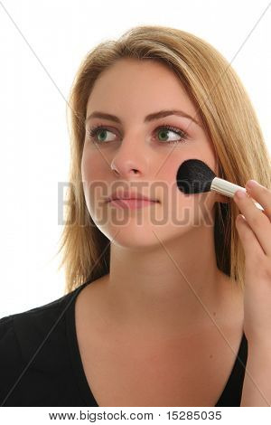Beautiful teenage girl applying her makeup