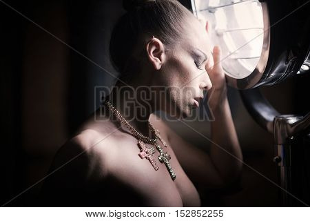 Nude girl with the evil eye possing in a studio