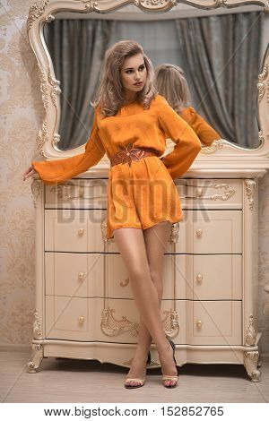 Elegant young woman in orange evening dress posing in vintage interior. Fashion shot.
