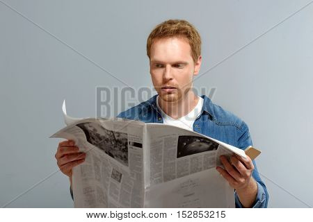 portrait of a bearded man reading news isolated on gray background with copy space
