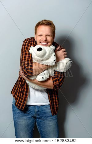 smiling adult person looking into camera while holding big teddy bear