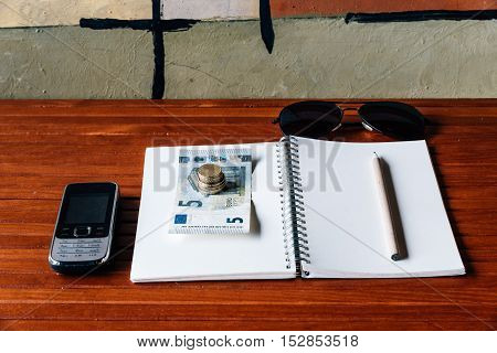 Blank notebook with pencil glasses cell phone and euro money on wooden desk