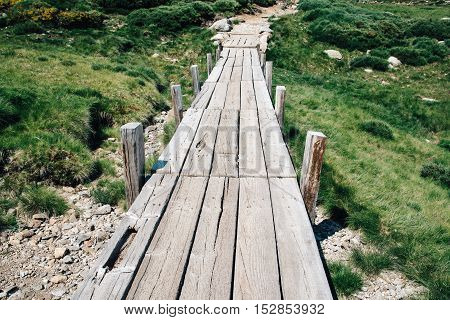 Small wooden bridge in the mountain a sunny day.