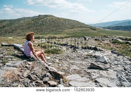 Middle age woman sitting in the rocks of the mountain a blue sky day.