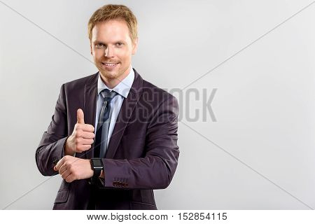 everything is alright, a happy manager in suit showing thumb up on white background with copy space