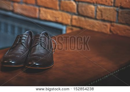 luxury men's footwear on the wood table over a brick background