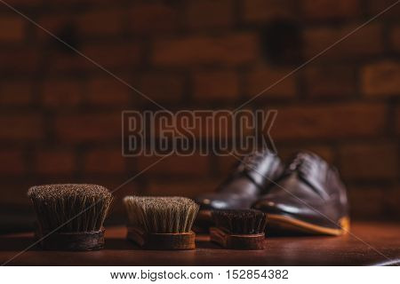 three brushes on the table with a pair of shoes on the table, selective focus