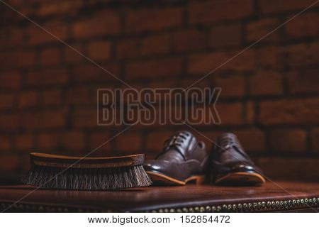 close up of a brush and pair of brogues on the old table