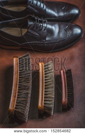 equipment for cleaning shoes on the table with a pair of boots, top view