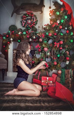 The beautiful young brunette decorates a New Year fir-tree