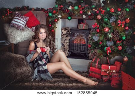 the beautiful young brunette sit near a Christmas tree and drink tea from a red mug.