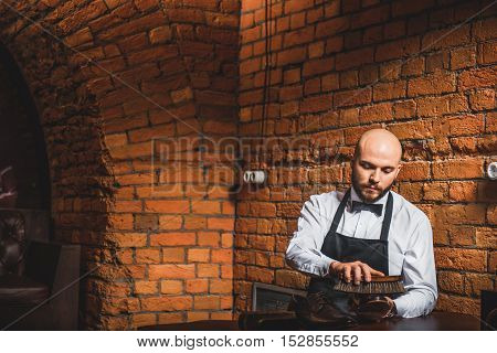 bearded bald man cleaning shoes with a brush over brick walls