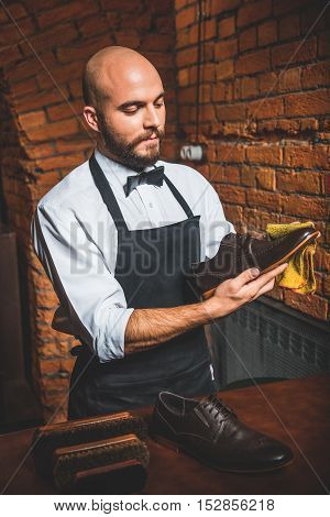 portrait of a man cleaning leather footwear with a rag