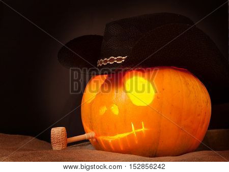 Pumpkin on Halloween in a cowboy hat with a pipe on an black background