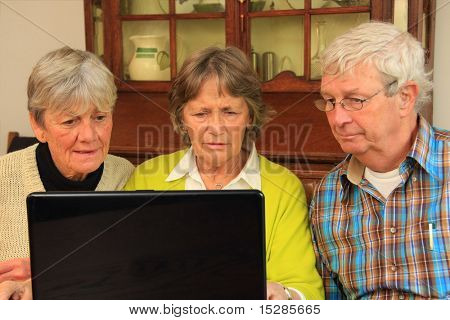 Three active senior citizens surfing the internet.