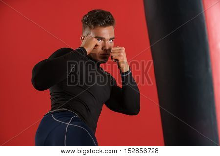 At gym. Photo of boxer fulfills blows, on red background