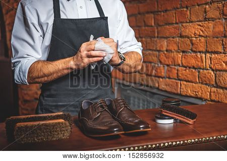 man in apron wipes his hands in front of the footwear