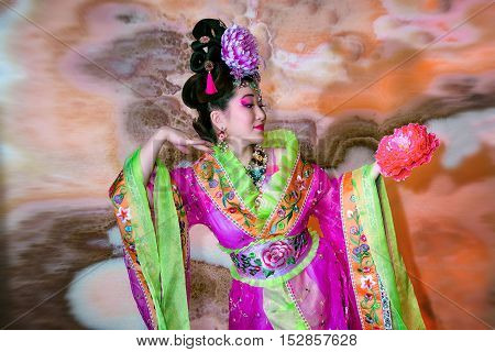 Beautiful Woman In A Traditional Chinese Outfit Holding A Flower