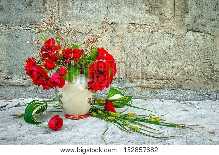 bouquet of red roses in vase near the concrete wall with copy space for your text