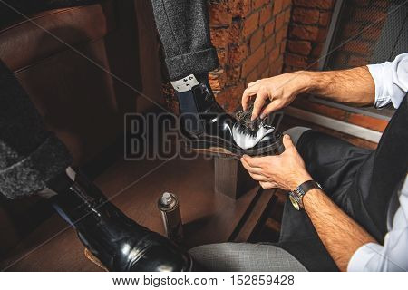 guy applying white gel on shoes with a sponge, close up