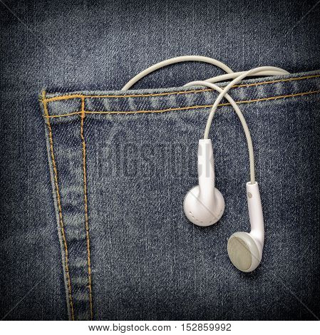 White Headphones hanging off a jeans pocket. Modern Earphones in a black jeans.