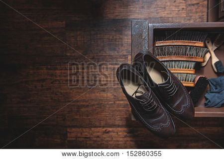 pair of brogues with camel hair brushes on the desk, over the wooden floor with copy space