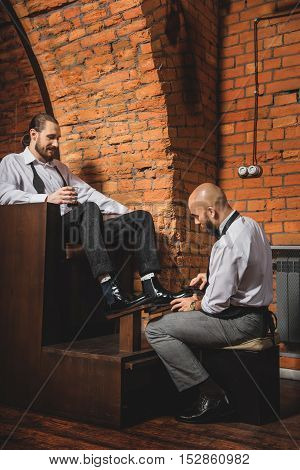 male sitting in front of the customer and brushing his leather shoes