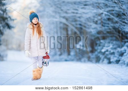 Cute little girl with flashlight having fun in winter day