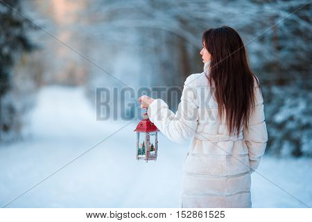 Winter beauty. Girl holding Christmas lantern outdoors on beautiful winter snow day