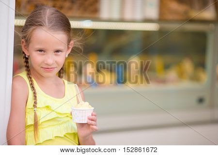 Adorable little girl eating ice-cream outdoors at summer