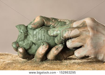 hands of ceramist moulding from blue clay