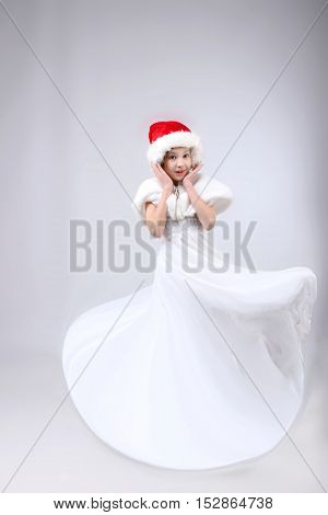 Christmas, X-mas, holidays, children, people concept - portrait of surprised little girl in Santa helper hat and long white dress over light background