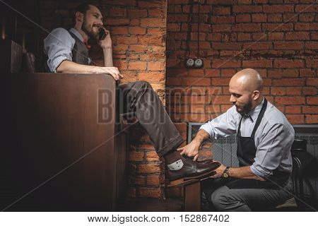 man sitting in a chair and talking on the phone while craftsman polishing shoes, close up