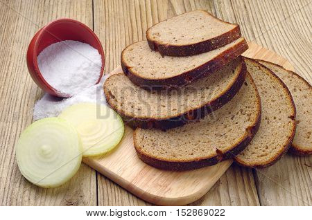 Sliced bread onion and salt on wooden background