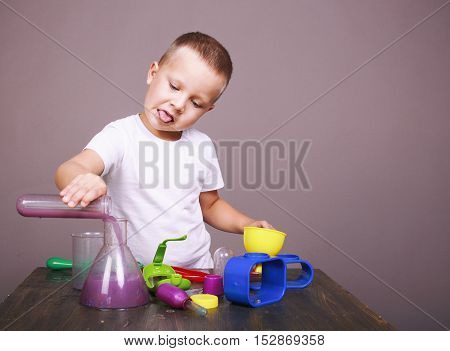cute kid doing chemistry experiments. boy holding flask and test tube in hands. child sticking his tongue out of zeal. empty space for your text