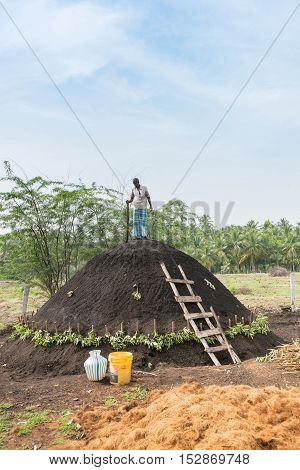 Dindigul India - October 22 2013: A man on top of his charcoal hill of black earth which covers raw wood. The man fastens the black dirt by hammering it with a beam. The ancient way. Blue sky and green background.