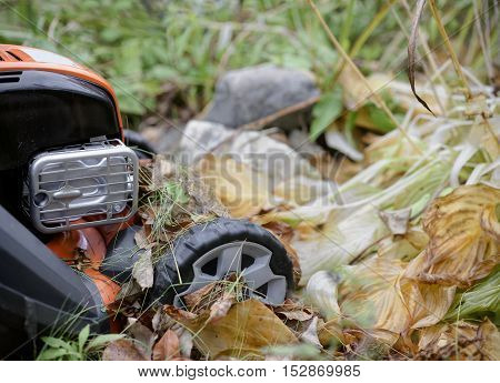 A lawn mower stuck in the autumn fallen leaves outdoor shot with selective focus