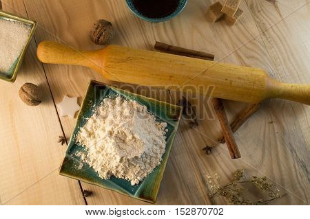 flour sugar and cinnamon on a wooden background