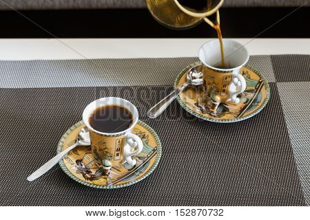 Morning coffee is poured from Cezve in beautiful cup with Egyptian pattern.