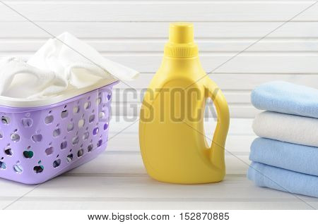 Dirty Cloth In A Plastic Purple Laundry Basket, Clean Folded Cloth And Blank Yellow Detergent Bottle