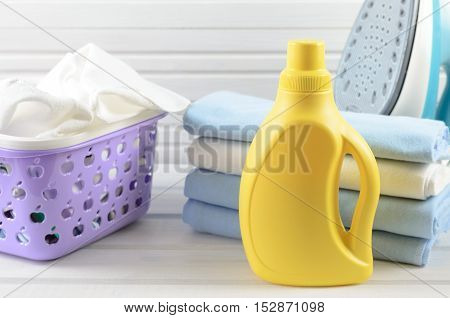 Dirty Cloth In A Plastic Purple Laundry Basket, Clean Folded And Ironed Cloth, Electric Iron And Bla