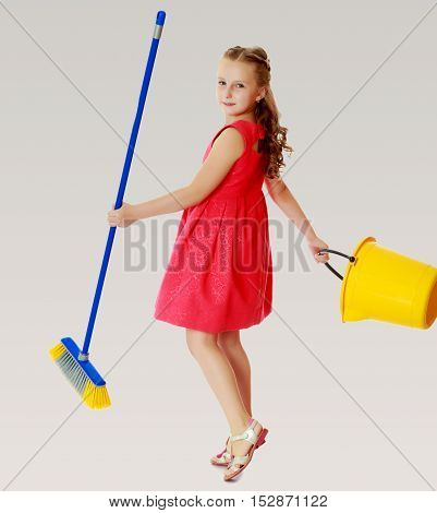 Beautiful little girl in a red short dress with a bucket and brush pleasure to cleans the house. On a gray background.