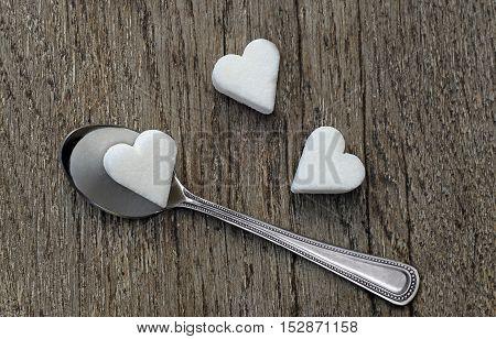 Three white sugar hearts with a tea spoon