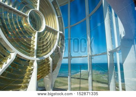 An up close view of the light of the Cape Agulhas lightouse with a view of the ocean in the background.