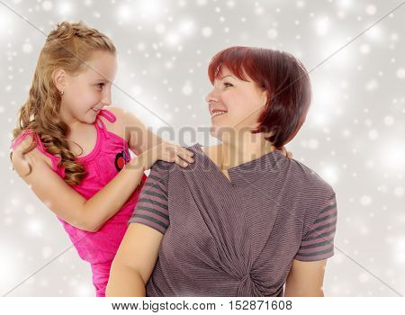 Happy family of two people, an adult mother, her beloved daughter 7 years. Daughter gently hugs the mother's neck. Close-up.Gray background with round white snowflakes.